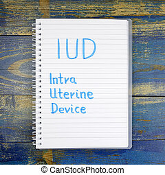 IUD- Intra Uterine Device written in notebook on wooden...