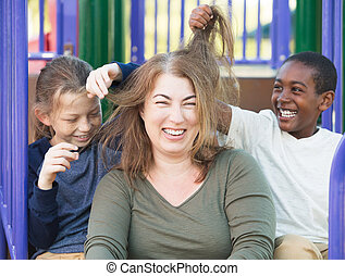 Sons playing with hair of mother - Laughing mother sitting...