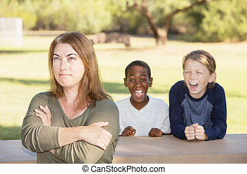 Frustrated mother with children at park - Frustrated mother...