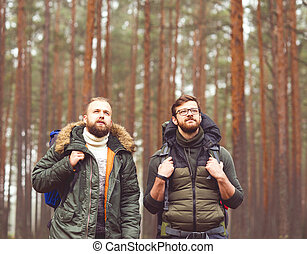 Man with a backpack and beard and his friend in forest -...