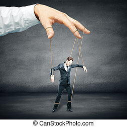 Control concept - Hand controlling businessman as puppet on...
