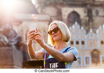 Beautiful young woman making selfy photo on her phone. -...
