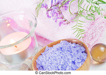 Spa setting with lilac flowers, bath salts and a candle