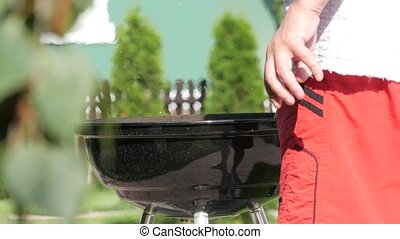 Man mixing charcoal in a barbecue gril with tongs. Handheld...
