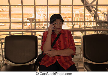 Mature elser asian woman is calling on a cell phone while...