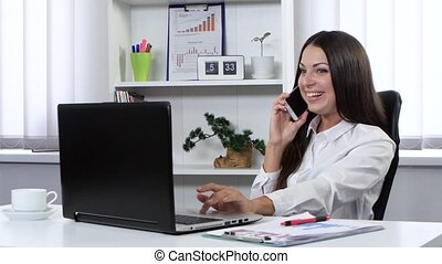 Business woman sitting in the office in front of a laptop and talking on the phone