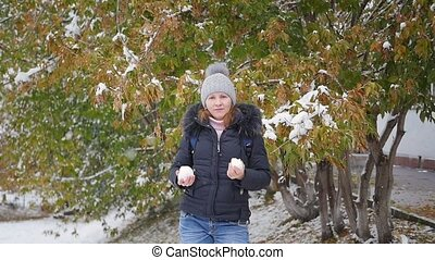 girl throws a snowball in the autumn park