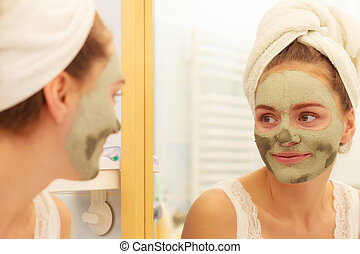 Woman face with green clay mud mask - Skin care. Woman in...