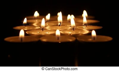 Small candles burning on a dark background. Close up -...
