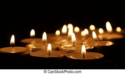Many burning small candles on dark background. Close up -...