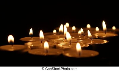 Tea candles burning in the darkness. ?lose up