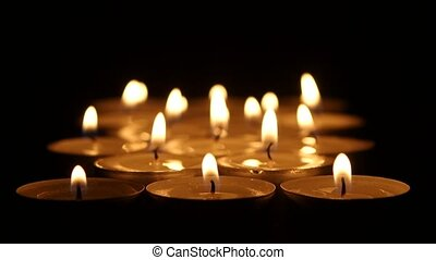 Group of burning candles on black background. Close up -...