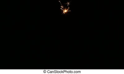 Lighting up a sparkler. Close up - Hand ignites sparkler,...