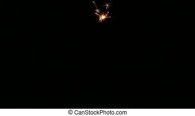 Lighting up a sparkler. Close up - Hand ignites sparkler,...