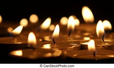 Brightly burning wax candles. Close up - Many candles, lit...