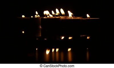 Group of burning small candles on a black background. Close...