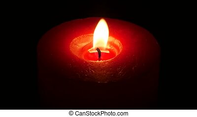 Beautiful red candle on dark. Close up - Fire from a candle,...