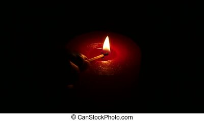 One red candle flame at night. Close up - Woman's hand...