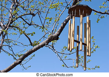 wind chimes in spring - opening tree buds against brilliant...