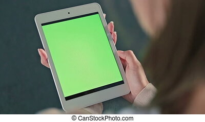 Woman looking at tablet with green screen. Close up shot of...