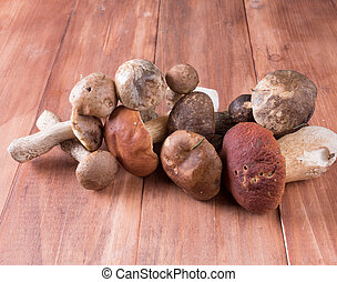 A mix of harvested mushrooms on old wooden background. -...