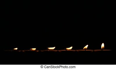 Six small candles in dark Close up - Six candles in the...