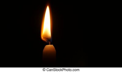 One candle flame at night. Close up - One candle is lit, a...