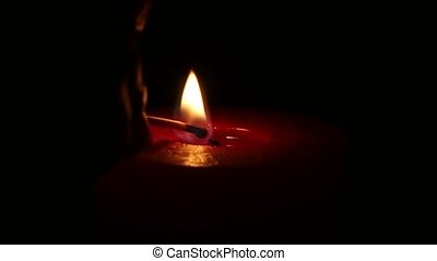 Burning red candle, isolated on the black background. Close...