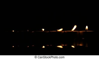 Six candles on a black reflecting background. Close up