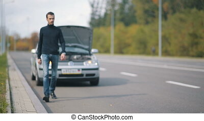 Man sitting on the road in a front of broken car
