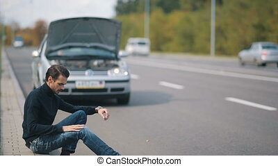 Man sitting in a front of broken car on the road - Road trip...