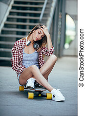young adult woman sitting on longboard and wearing headphones
