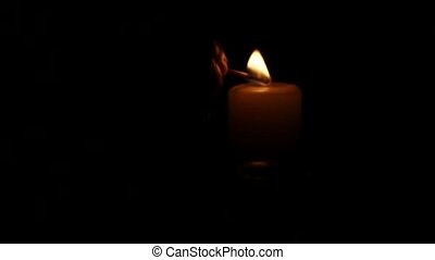 Bright burning candle in the dark. Close up. Slow motion -...