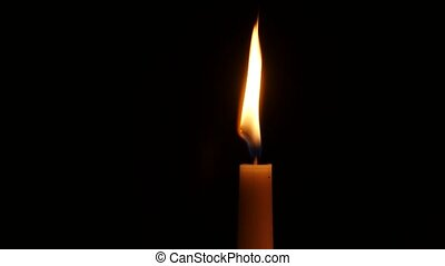Burning candle, isolated on the black background. Close up -...