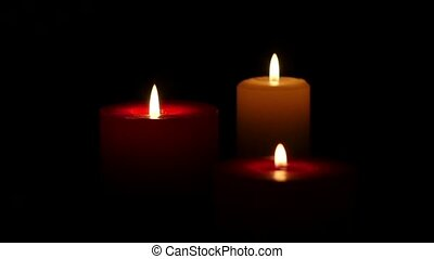 Three candles on dark background. Close up. Slow motion