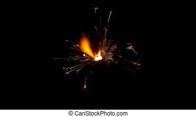 Sparkler burning over black background. Slow motion - Bengal...