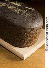 Loaf of rye bread on a wooden background