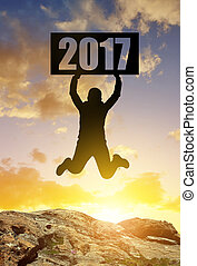 Concept New Year 2017 - Hiker jumps up in celebration of the...