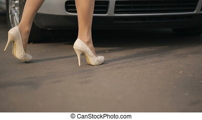 Womans feet cominng to car