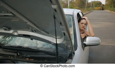 Sad Woman in broken car - Road trip car trouble. A young...