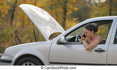 Woman in a broken car talking by the phone - Road trip car...