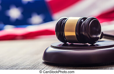 Judges wooden gavel with USA flag in the background. Symbol for jurisdiction