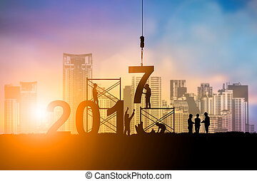 Silhouette employees work as a team to change the 6 to 7 prepared to welcome the New Year over blurred sunset. Teamwork, success, Industry, Business, People, engineers, working a systematic concept.