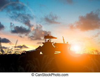 silhouette Farmer in tractor preparing land with seedbed...