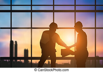 Silhouette engineer construction industry stands shake hands with the construction team and construction contract business over blurred pastel background sunset industry. Heavy industry concept.