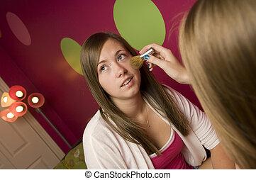 Teenagers applying makeup - Teenage girls apply makeup in...