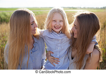 beautiful young mother and her daughters at the wheat field