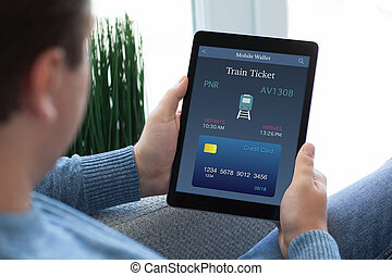 man in jeans holding tablet computer with online train ticket