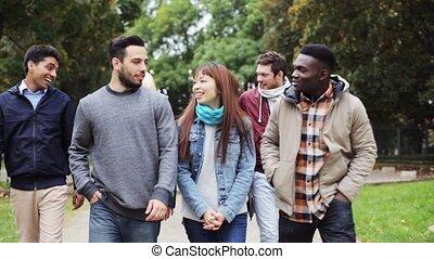 happy friends walking along autumn park - people,...