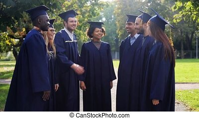 happy students in mortar boards making high five -...